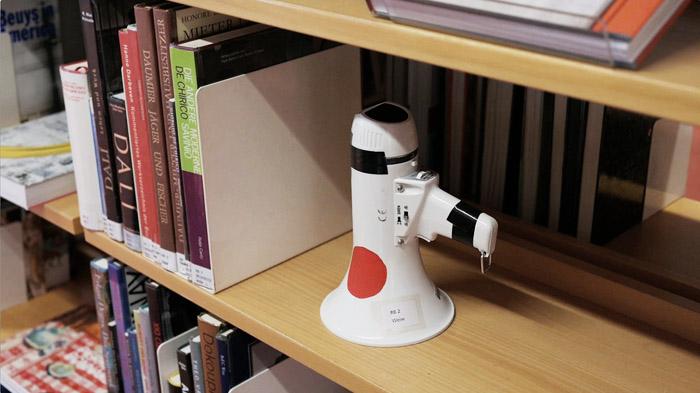 N. entdeckt ein Megaphon im Regal der Stadtbücherei - und leiht es aus. (Videostill)